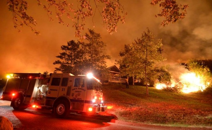 Firefighters protecting property from a wildfire