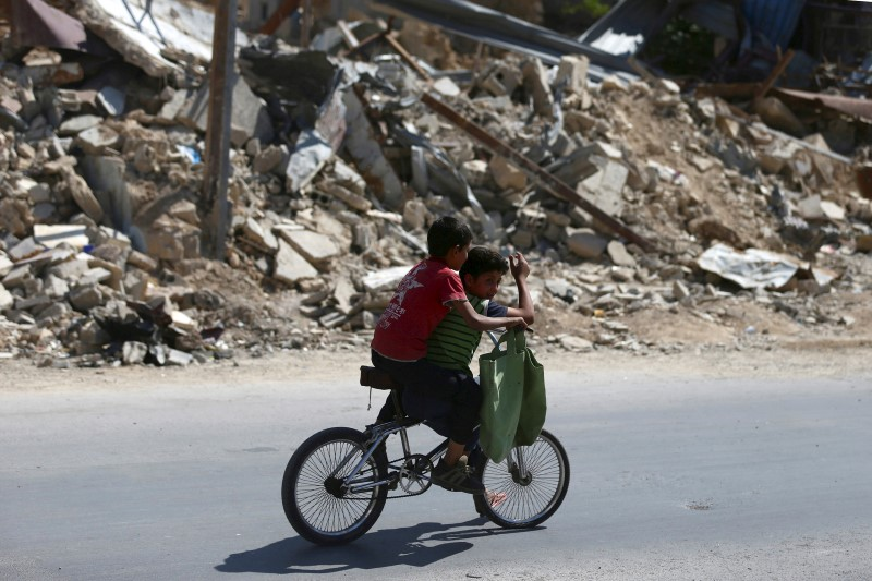 Boys on motorcycle near rubble