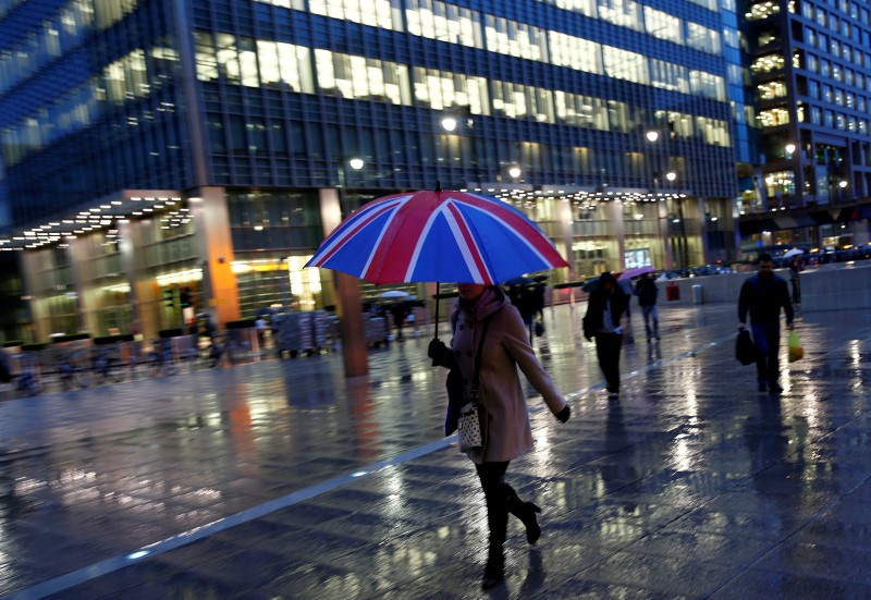 Workers walk in the rain at the Canary Wharf business district in London, Britain