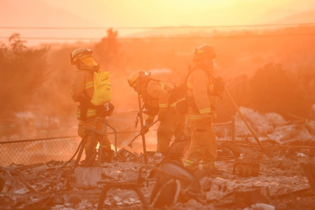 Visalia firefighters extinguish hot spots at a residence leveled by the Erskine Fire in South Lake, California, U.S.