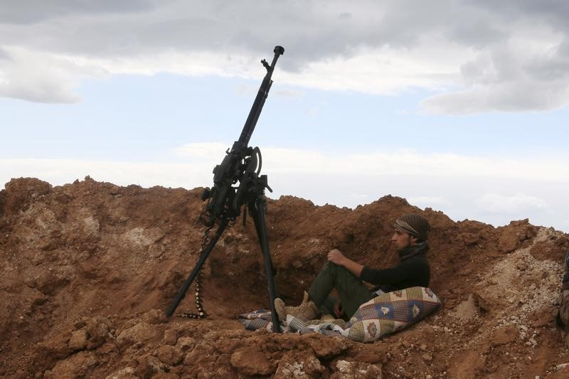 A rebel fighter sits near a weapon in Al-Lataminah village, northern Hama countryside, Syria