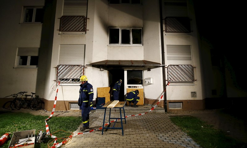 Members of Germany's technical support unit fix wooden boards to a building used to house asylum seekers after a fire broke out