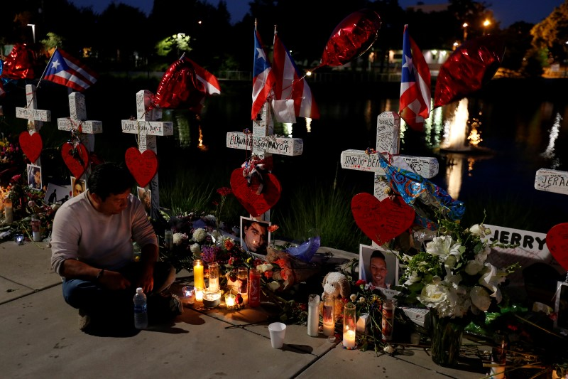 Jose Louis Morales sits and prays under his brother Edward Sotomayor Jr.'s cross that is part of a makeshift memorial for the victims of the Pulse night club shootings in Orlando