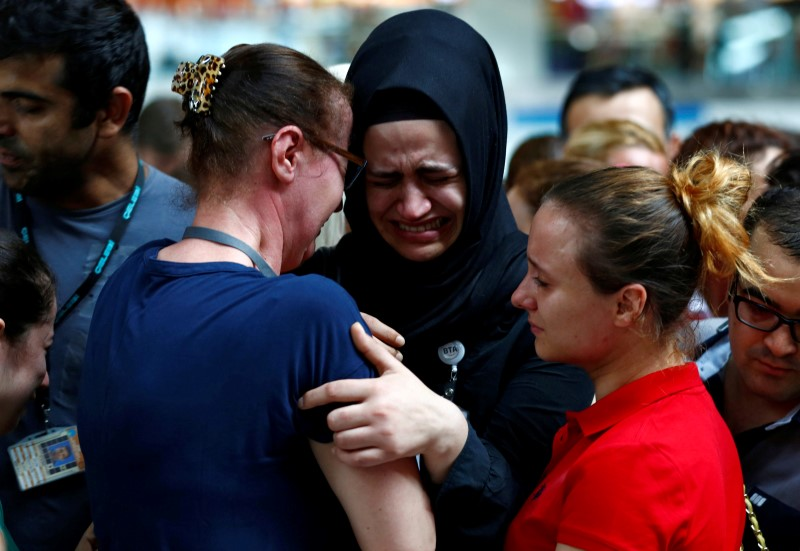 Airport employees mourn for their friends, who were killed in Tuesday's attack at the airport, during a ceremony at the international departure terminal of Ataturk airport in Turkey