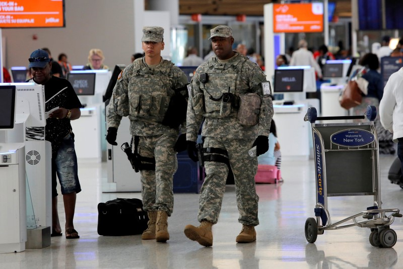 Members of the U.S. Army monitor the departures area at John F. Kennedy international Airport in the Queens borough of New