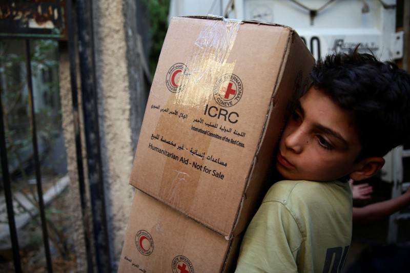 A boy unloads aid parcels in the rebel-held besieged town of Zamalka, in the Damascus suburbs