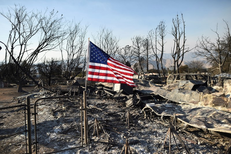 An American flag flies above wreckage at a residence leveled by the Erskine Fire in South Lake