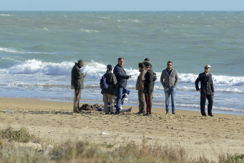 People stand next to the dead body of a migrant on the beach of Siculiana, in Western Sicily, Italy,