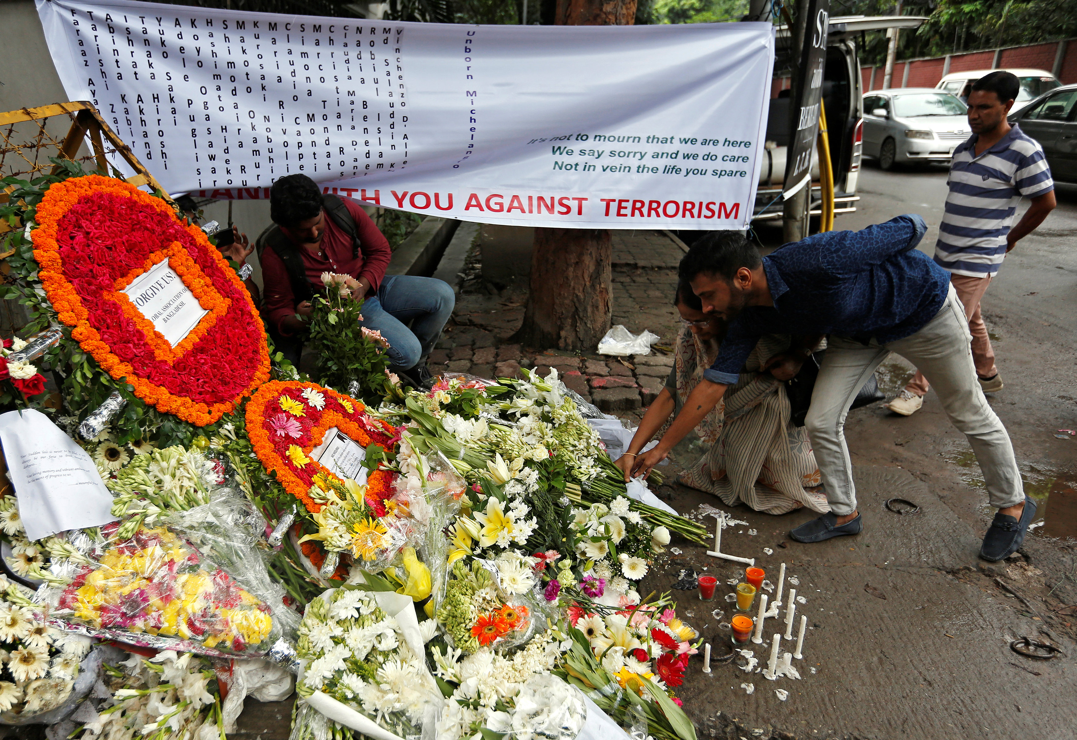 People place flowers at a makeshift memorial near the site, to pay tribute to the victims of the attack on the Holey Artisan Bakery and the O'Kitchen Restaurant, in Dhaka