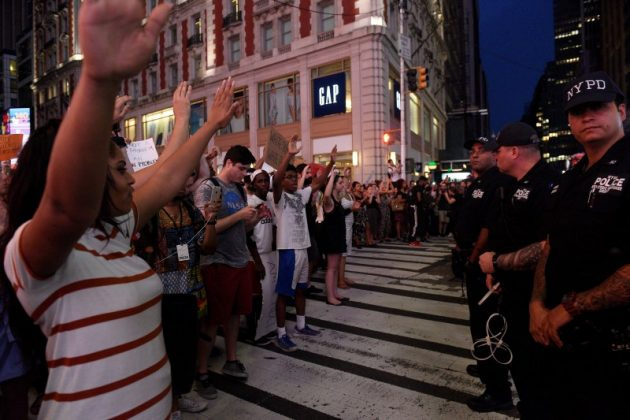 """People hold their hands in the air as they yell """"hands up, don't shoot!"""" during a protest for the killing of Alton Sterling and Philando Castile in the Manhattan borough of New York"""