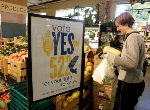 A customer picks up produce near a sign supporting a ballot initiative in Washington state that would require labelling of foods containing genetically modified crops at the Central Co-op in Seattle, Washington October 29, 2013. REUTERS/Jason Redmond