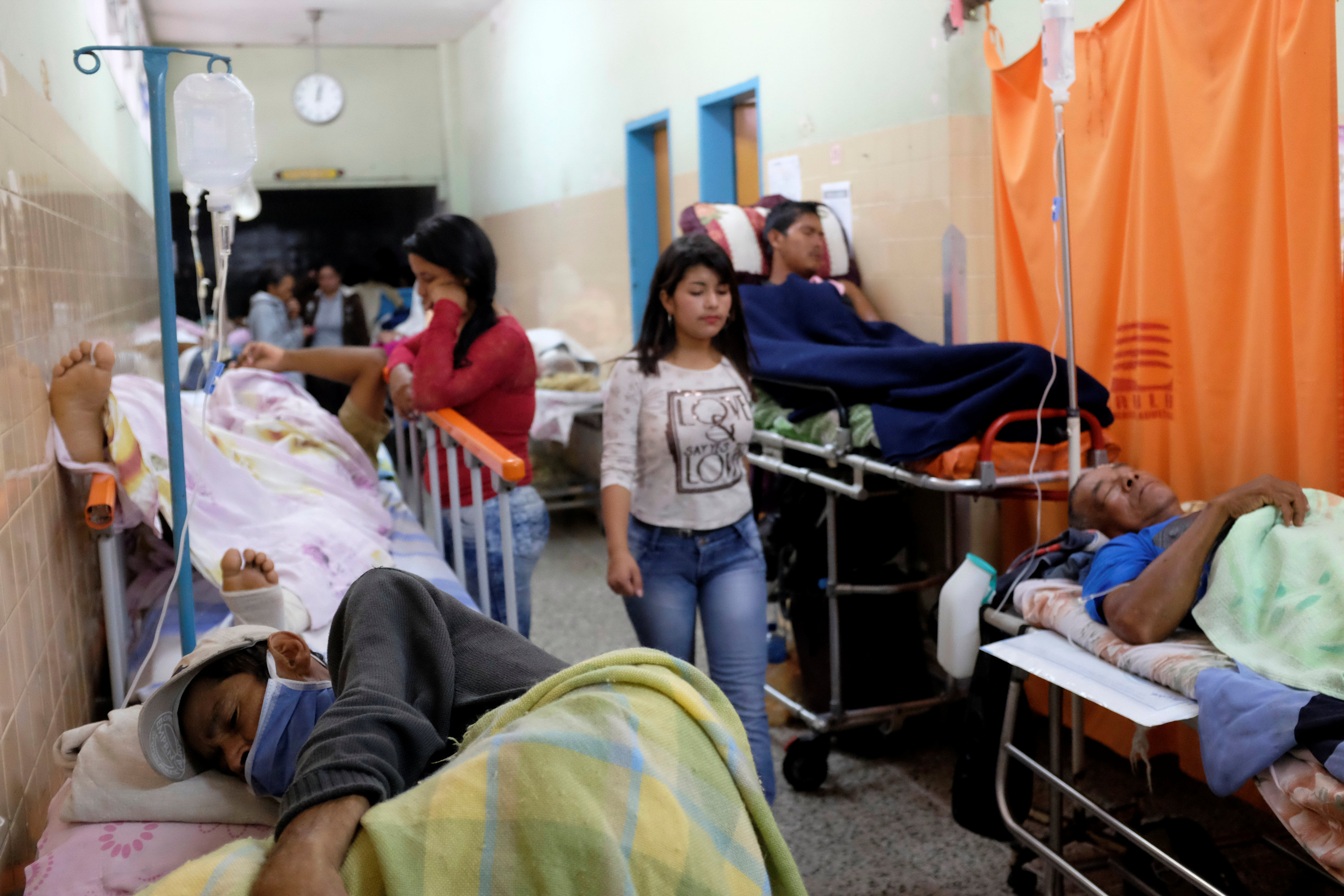 Patients lie in hospital beds in the hallway of Venezuelan hospital