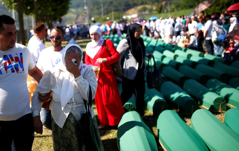 Muslim woman cries near coffins of her relatives, who are newly identified victims of the 1995 Srebrenica massacre, which are lined up for a joint burial in Potocari