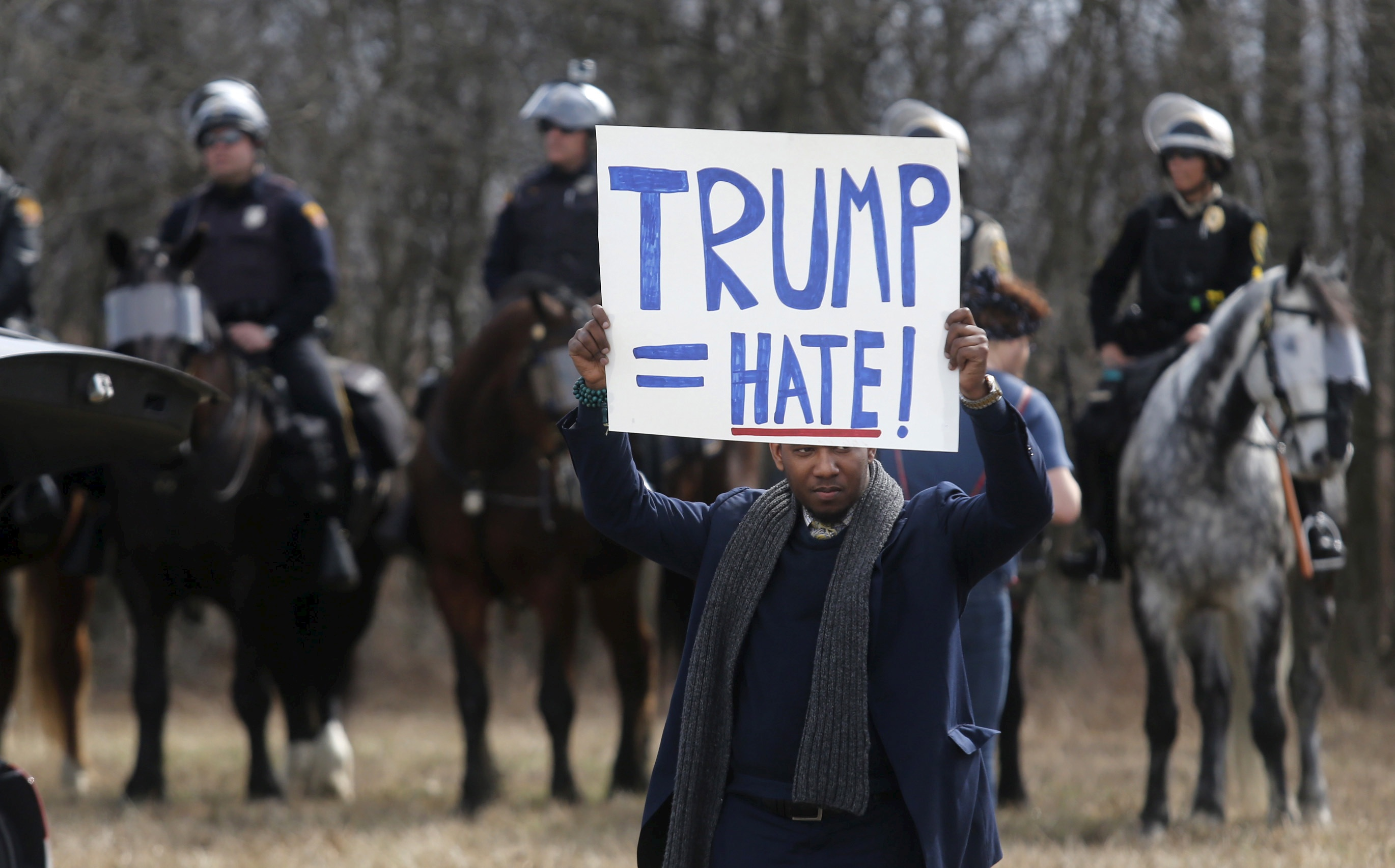 An anti-Trump protester holds his protest sign in front of mounted police outside a rally for Republican U.S. presidential candidate
