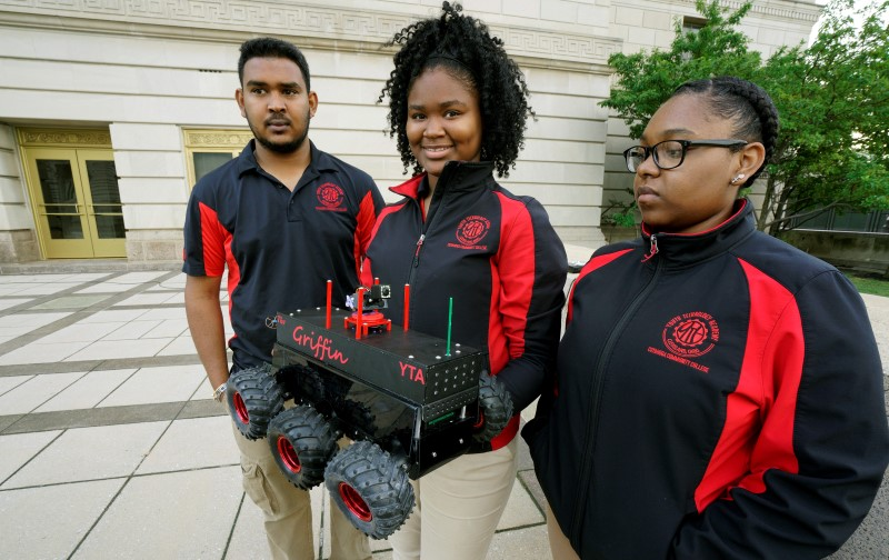 Students Iris Harris and Domonique Dumas with their mentor Kevin Sarran display their Griffin scout robot that will be used by police during a demonstration of police capabilities near the site of the Republican National Convention in Cleveland,