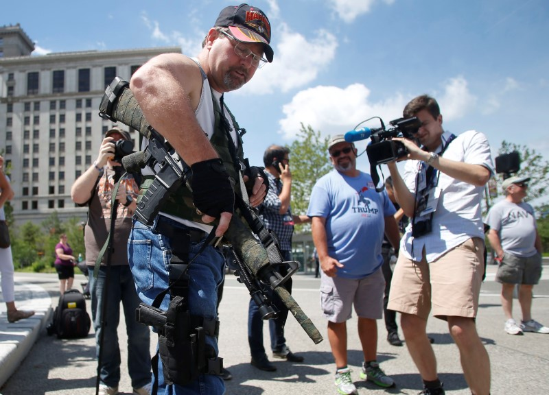 Steve Thacker with a rifle and a handgun is surrounded by members of the news media in