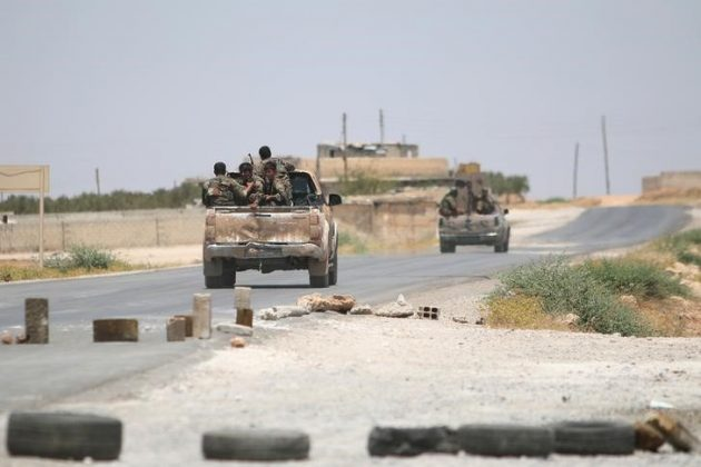 Syria Democratic Forces (SDF) ride vehicles along a road near Manbij, in Aleppo Governorate, Syria,