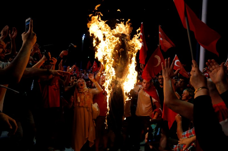 Supporters of Turkish President Tayyip Erdogan shout slogans over a burning effigy of U.S.-based cleric Fethullah Gulen during a pro-government demonstration at Taksim Square in Istanbul, Turkey