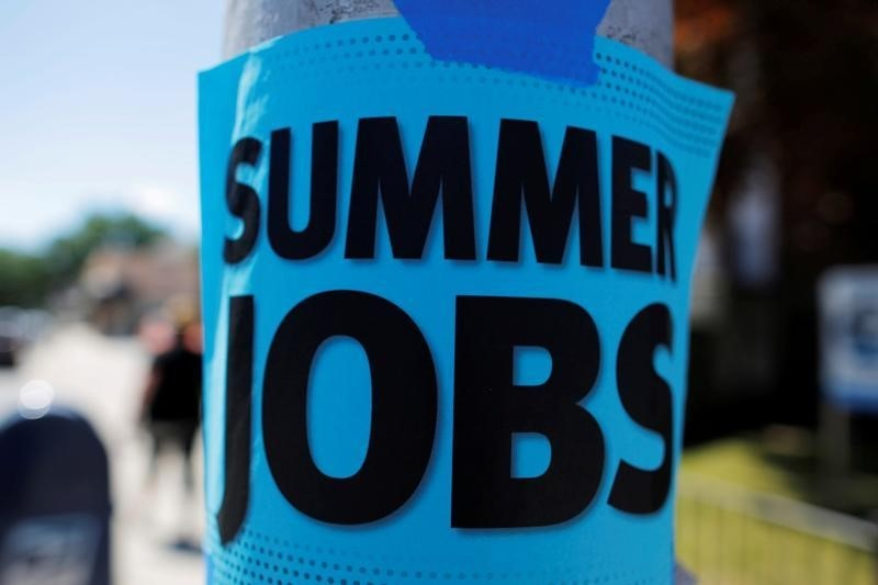 "A sign advertising ""Summer Jobs"" hangs on a lamp post in Somerville, Massachusetts,"