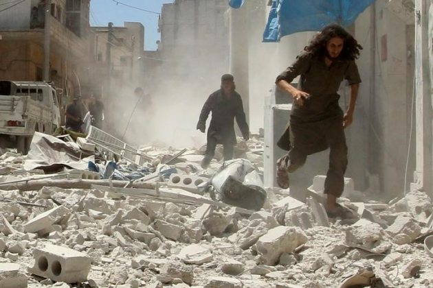 Men make their way through the rubble of damaged buildings at a site hit by air strikes in Idlib city, Syria