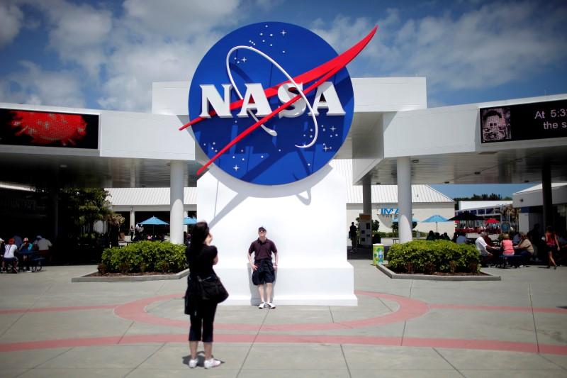 ourists take pictures of a NASA sign at the Kennedy Space Center visitors complex in Cape Canaveral, Florida