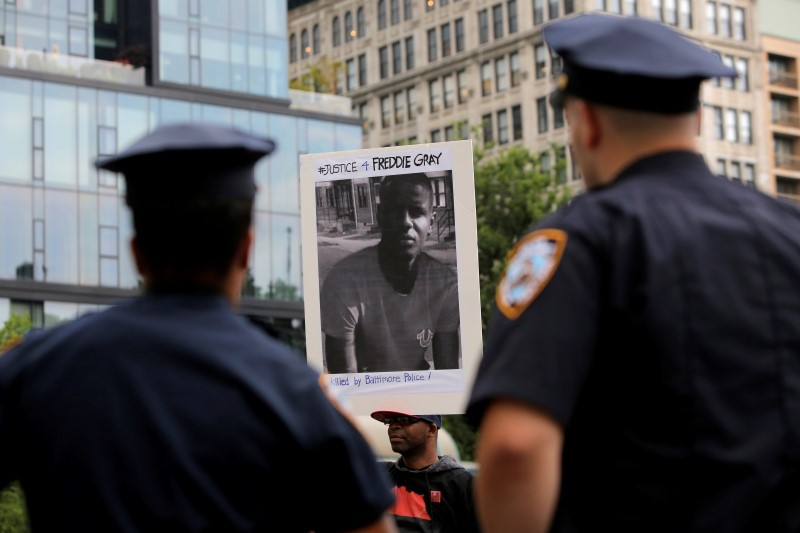 Police watch on as a man participates in a protest in Union Square after Baltimore Police Officer Caesar Goodson Jr. was acquitted of all charges for his involvement in the death of Freddie Gray in the Manhattan borough of New York