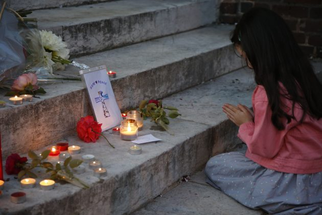 A young girl prays near flowers and candles at the city hall in Saint-Etienne-du-Rouvray to pay tribute to Father Jacques Hamel, who was killed in an attack on a church