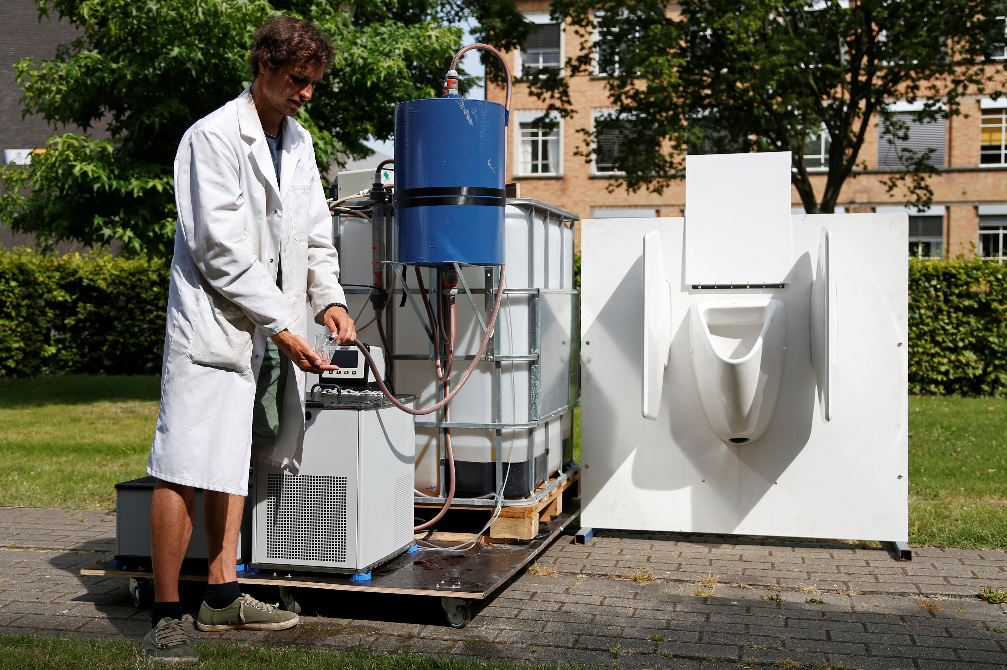Belgian scientist Derese pours water from a machine that turns urine into drinkable water and fertilizer using solar energy, at the University of Ghent