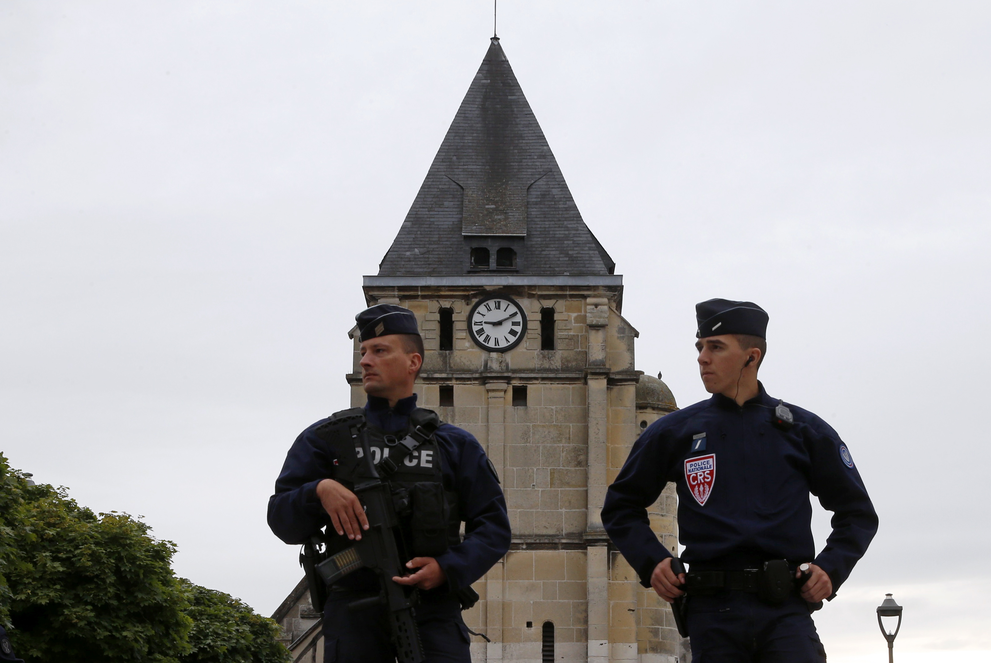 French police guard stand in front of church