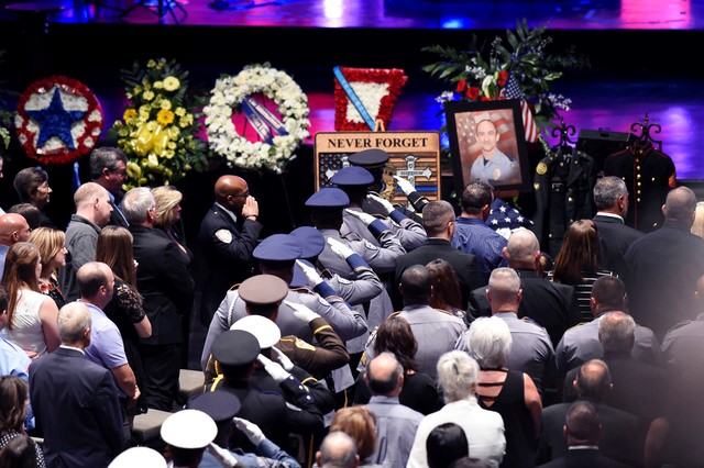 police saluting the caskets of fallen police officers