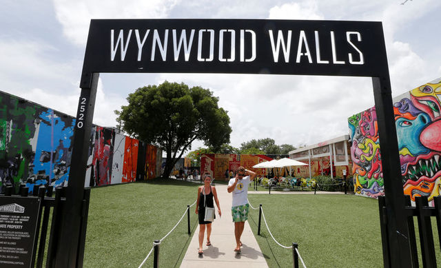 Visitors walk through the Wynwood arts district of Miami