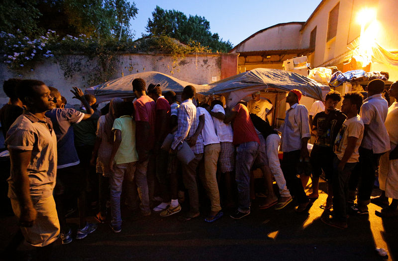 Migrants queue for food at a makeshift camp in Via Cupa (Gloomy Street) in downtown Rome, Italy,