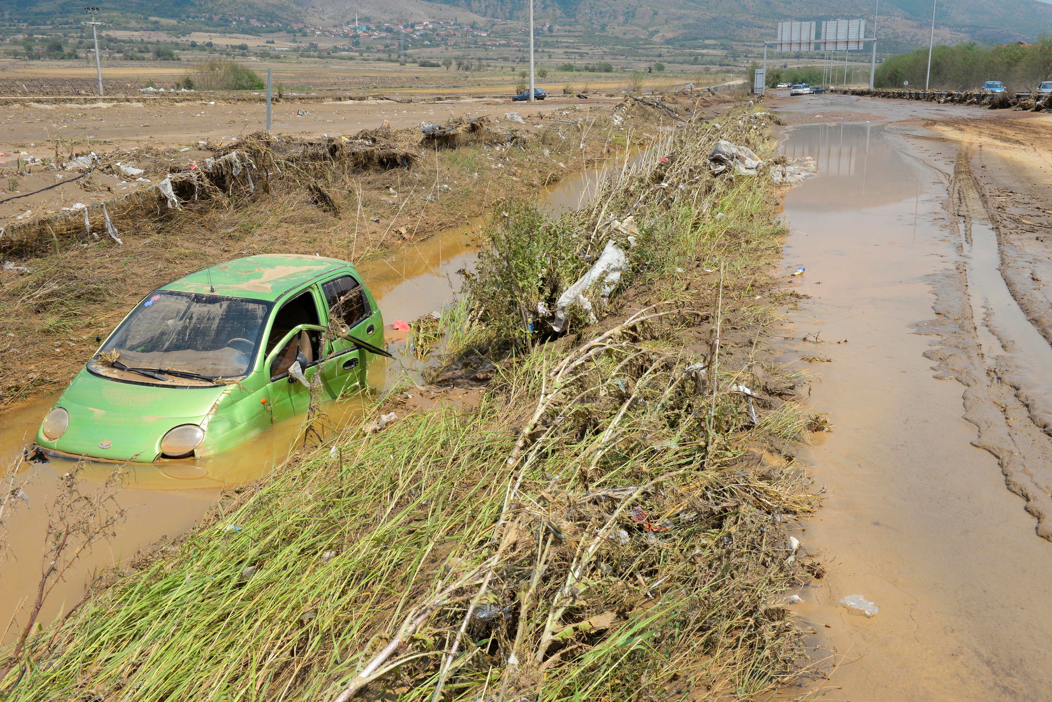 A wrecked car is seen after heavy floods in Cento