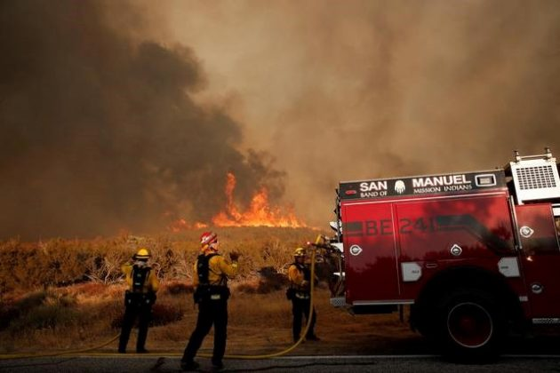 Firefighters prepare hose lines to attempt to hold a road during the Pilot Fire near Silverwood Lake in San Bernardino county near Hesperia, California, U.S.