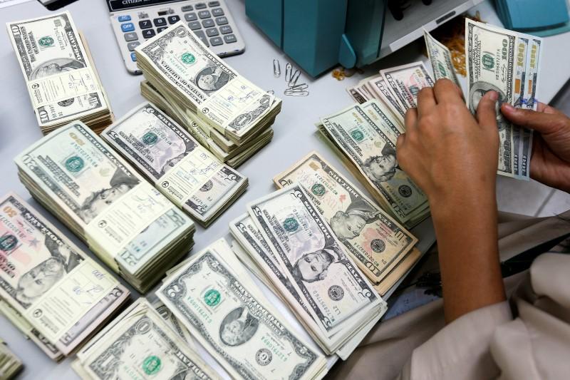 A bank employee counts U.S. dollar notes at a Kasikornbank in Bangkok, Thailand