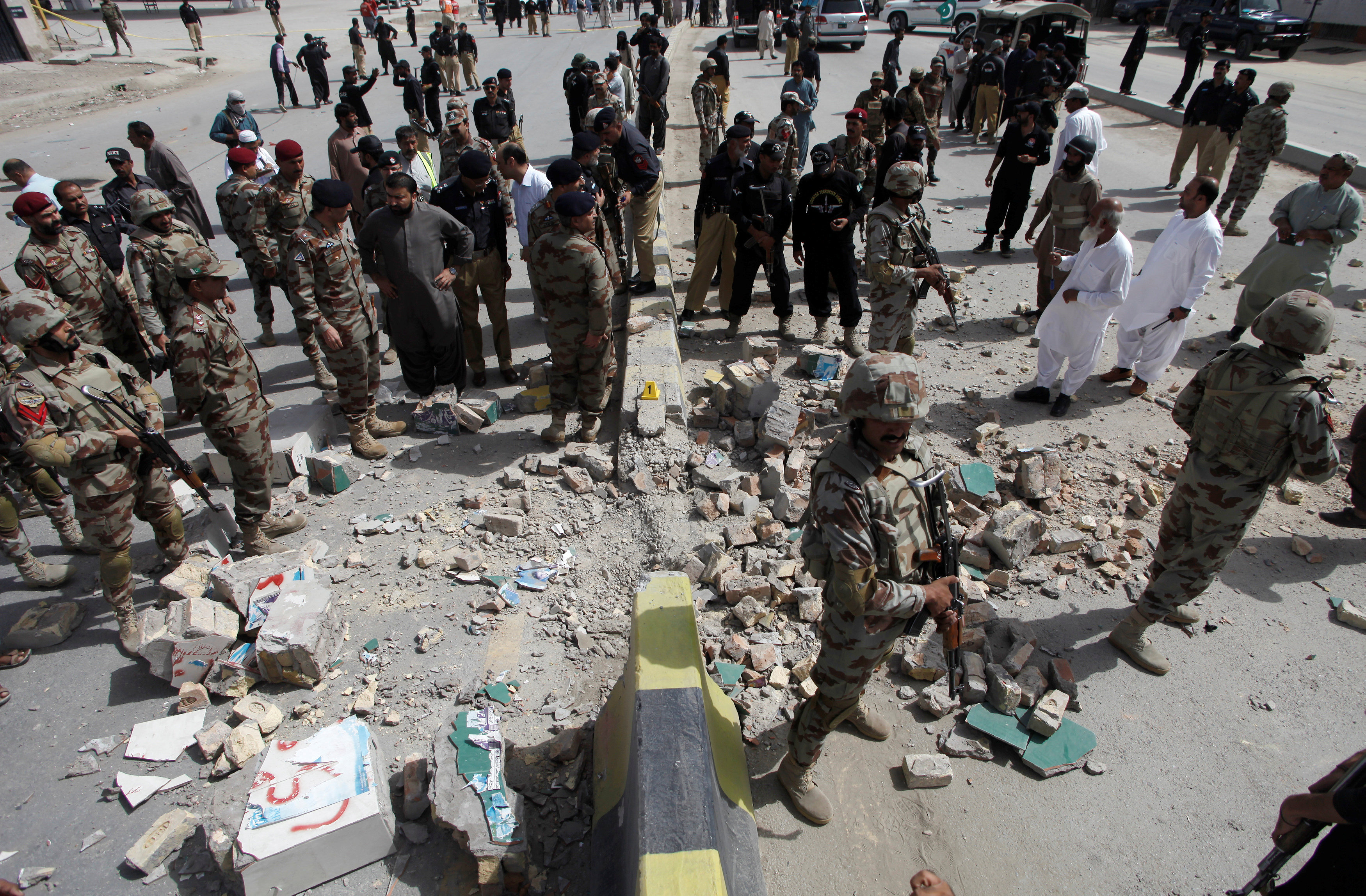Security officials gather at the site of a bomb explosion in Quetta, Pakistan,