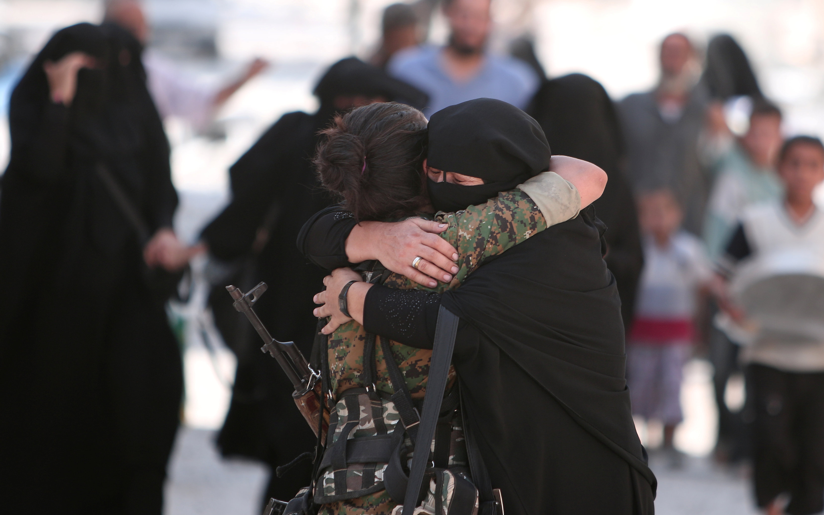 A woman embraces a Syria Democratic Forces (SDF) fighter after she was evacuated with others by the SDF from an Islamic State-controlled neighbourhood of Manbij
