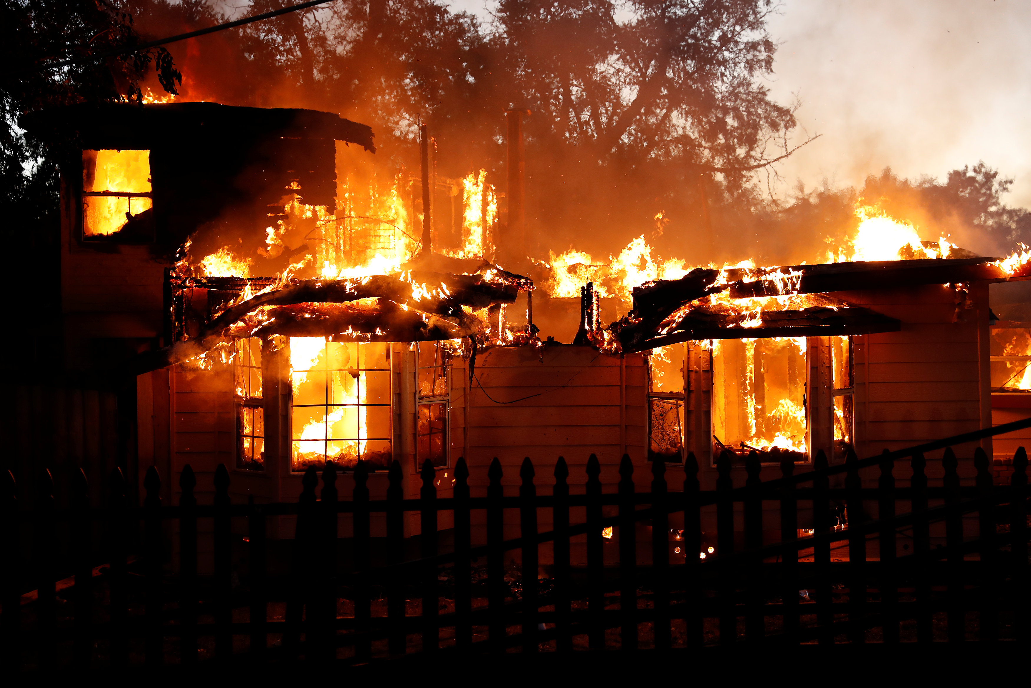A burning house damaged by the Clayton Fire is seen near Lower Lake in California,