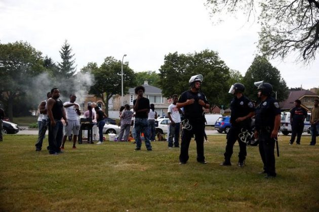 Police and community members stand in a park after disturbances following the police shooting of a man in Milwaukee, Wisconsin,