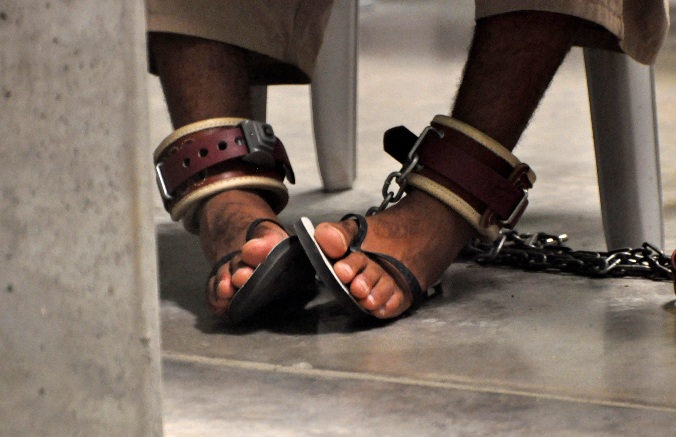 """n this photo, reviewed by a U.S. Department of Defense official, a Guantanamo detainee's feet are shackled to the floor as he attends a """"Life Skills"""" class inside the Camp 6 high-security detention facility at Guantanamo Bay U.S"""