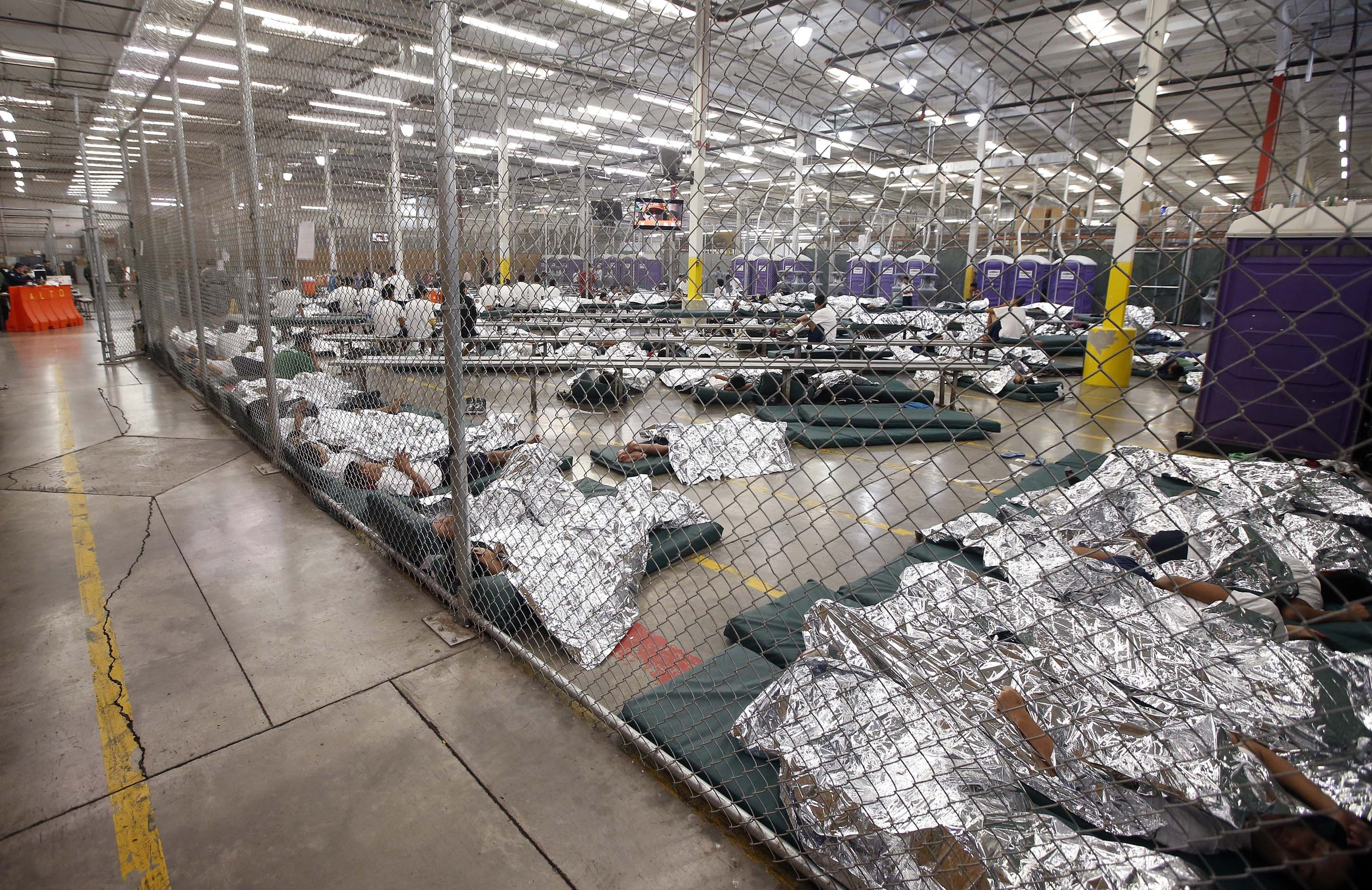 Detainees sleep and watch television in a holding cell where hundreds of mostly Central American immigrant children are being processed and held at the U.S. Customs and Border Protection
