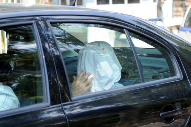 One of the eight Turkish soldiers, who fled to Greece in a helicopter and requested political asylum after a failed military coup against the government, is seen in a police car with his face covered.