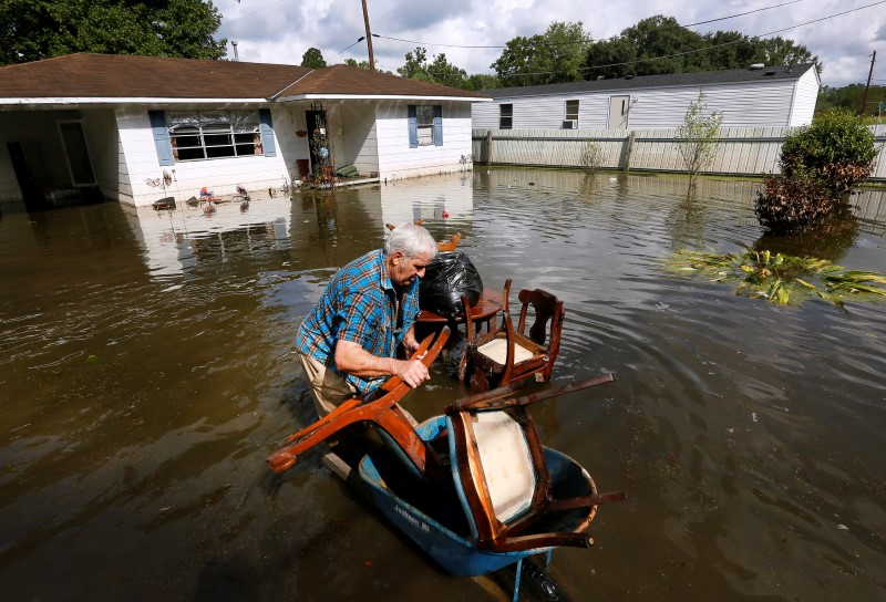 Paul Labatut carries damaged furniture through flood water outside her home in St. Amant, Louisiana, U.S