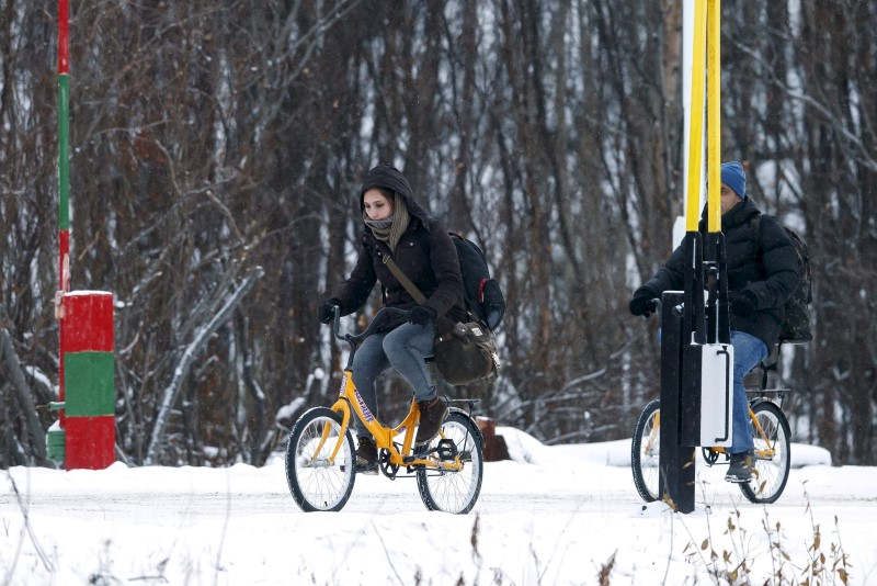 Two migrants on bicycles cross the border between Norway and Russia in Storskog near Kirkenes in Northern Norway