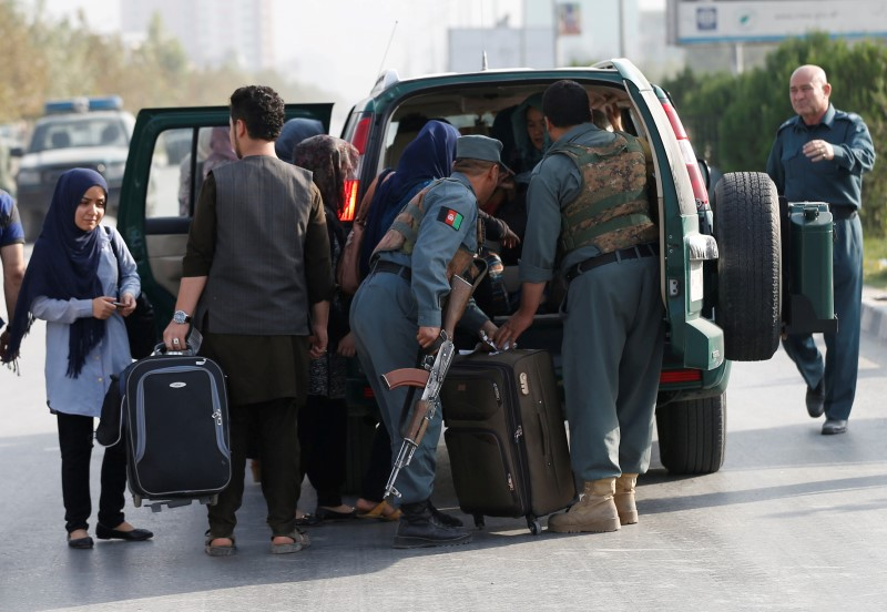 tudents walk toward a police vehicle after they were rescued from the site of an attack at the American University of Afghanistan in