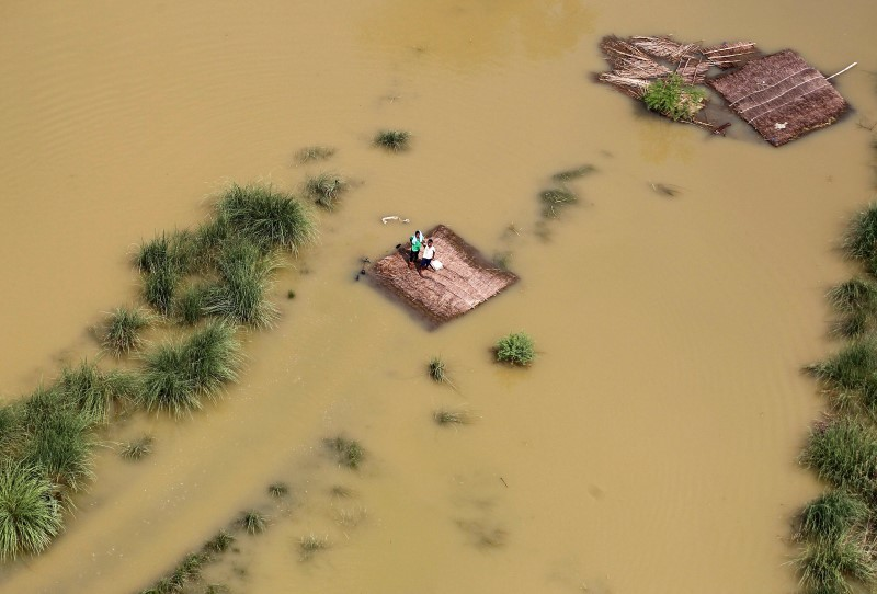 People stand on a partially submerged house as they wait to receive food parcels being distributed by a Indian Air Force helicopter on the outskirts of Allahabad,
