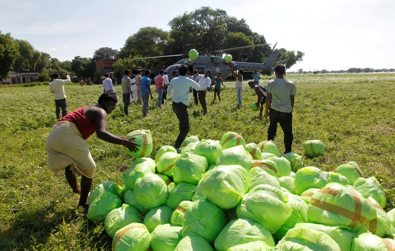 People unload relief food material from an Indian Air Force helicopter to be distributed among the flood victims, on the outskirts of Allahabad, India,
