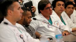 Gunshot survivor Angel Colon is surrounded by doctors as he listens to remarks at a news conference at the Orlando Regional Medical Center o