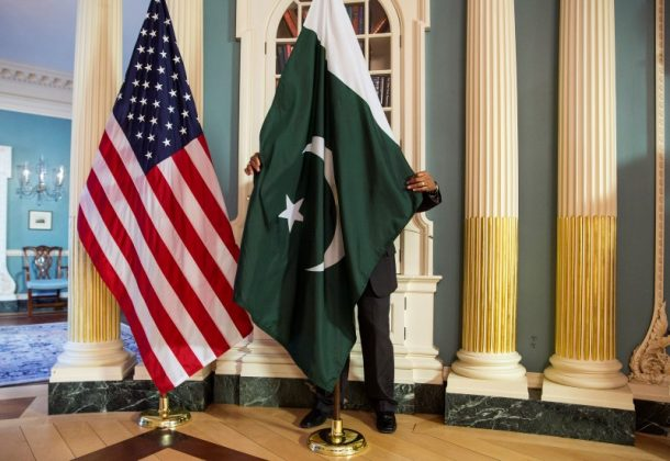 A State Department contractor adjust a Pakistan national flag before a meeting between U.S. Secretary of State John Kerry and Pakistan's Interior Minister Chaudhry Nisar Ali Khan on the sidelines of the White House Summit on Countering Violent Extremism at the State Department in Washington February 19, 2015.
