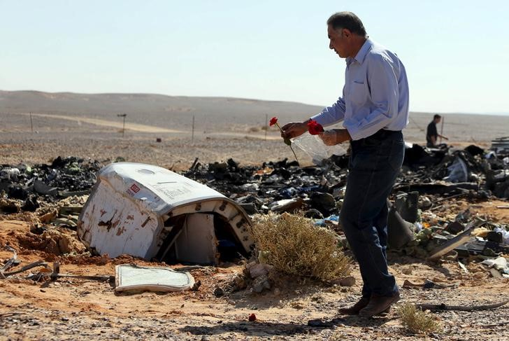 An Egyptian man puts flowers near debris at the crash site of a Russian airliner in al-Hasanah area at El Arish city, north Egypt, November 1, 2015.
